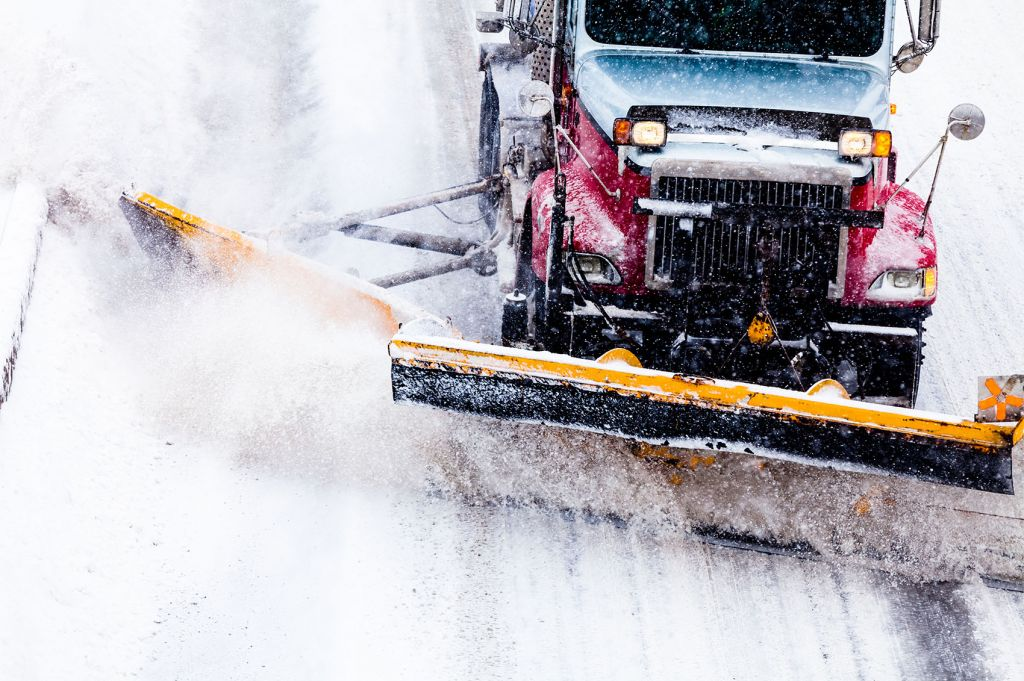 Snowplow Truck Removing the Snow from the Highway during a Snowstorm