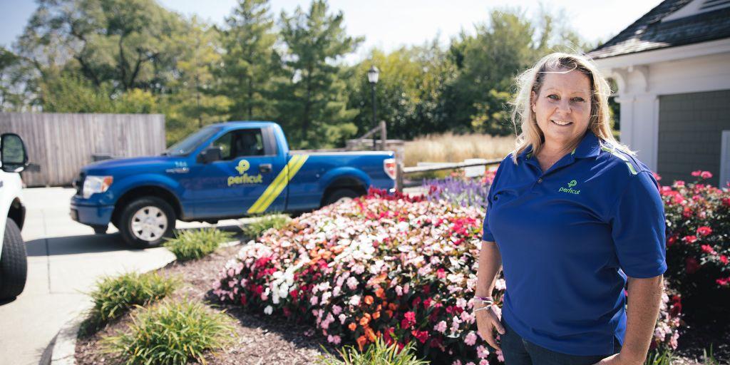 Lisa Fazio standing in front of flowerbed