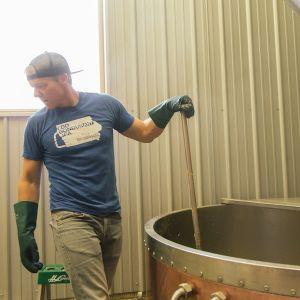 Man stirring tank at brewery