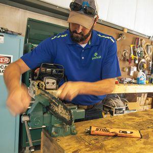 Perficut Team Member Fixing A Chainsaw
