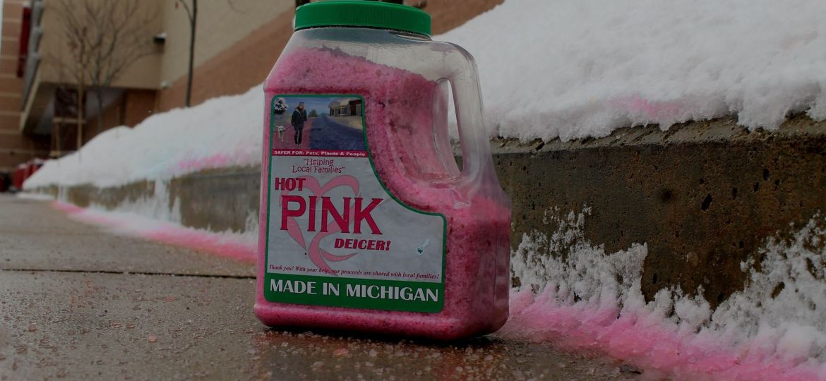 A bottle of Hot Pink Deicer on a sidewalk