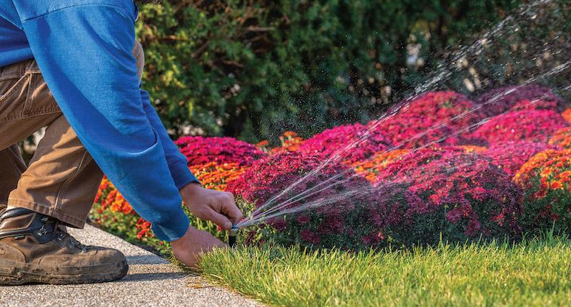 Technician adjusting irrigation system sprinkler