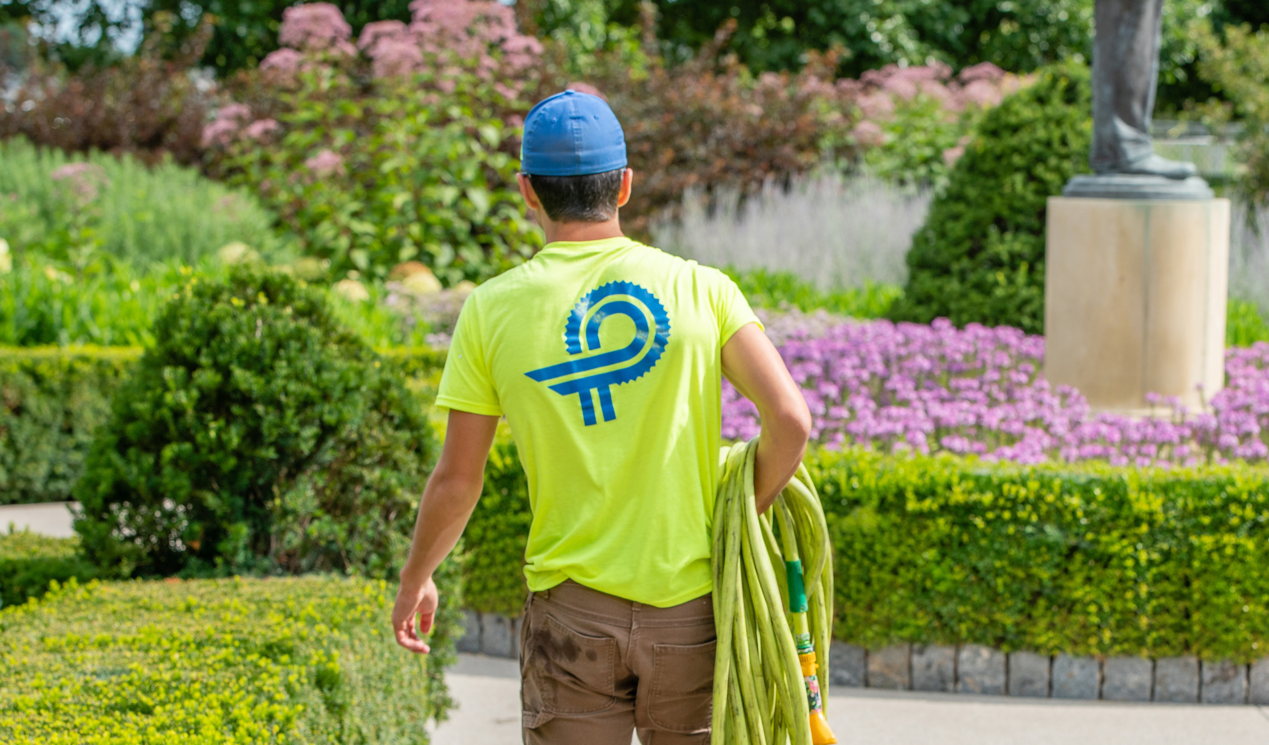 Perficut Employee Carrying Hose To Water Flowers